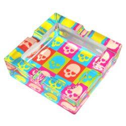 Cigaretový popelník skleněný Skull-Masivní cigaretový popelník skleněný. Hranatý popelník na cigarety s čtyřmi odkládacími místy je vyrobený ze silného skla. Dno je potištěné barevným motivem. Rozměry popelníku: 12x12x3,9cm. Popelník je dodávaný v kartonové krabici.