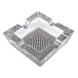 Cigaretový popelník skleněný Cubes-Cigaretový popelník skleněný Cubes. Hranatý popelník na cigarety se čtyřmi odkládacími místy je vyrobený ze silného skla. Díky větší šířce dvou odkládacích míst, je tento popelník vhodný také pro doutníky. Tloušťka stěny je 1,4cm. Dno popelníku je potištěné atraktivním barevným motivem. Rozměry popelníku: 10x10x3,1cm. Popelník je dodávaný v kartonové krabičce.