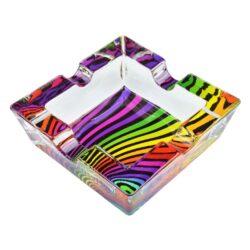 Cigaretový popelník skleněný Waves-Cigaretový popelník skleněný Waves. Hranatý popelník na cigarety se čtyřmi odkládacími místy je vyrobený ze silného skla. Díky větší šířce dvou odkládacích míst, je tento popelník vhodný také pro doutníky. Tloušťka stěny je 1,4cm. Dno popelníku je potištěné atraktivním barevným motivem. Rozměry popelníku: 10x10x3,1cm. Popelník je dodávaný v kartonové krabičce.