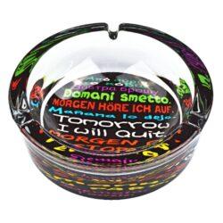 Cigaretový popelník skleněný kulatý Color text-Masivní cigaretový popelník skleněný. Kulatý popelník na cigarety se třemi odkládacími místy je vyrobený ze silného skla. Tloušťka stěny je 1,2cm. Dno popelníku je potištěné atraktivním barevným motivem. Průměr popelníku 13cm, výška 4,4cm. Popelník je dodávaný v kartonové krabičce.