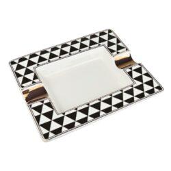 Doutníkový popelník keramický Triangles-Atraktivní doutníkový popelník na 2 doutníky. Hranatý keramický popelník ve tvaru obdélníku s bíločerným motivem je zdobený zlatými prvky. Kvalitně zpracovaný glazurovaný povrch popelníku je v lesklém provedení. Popelník na doutníky je dodávaný v dárkové krabičce. Rozměry popelníku: 20,5x17,2x3,1cm.
