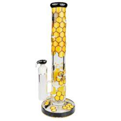 Skleněný bong s perkolací Grace Glass Beehive Series Ice, 42cm-Masivní skleněný bong s perkolací Grace Glass Beehive Series. Precizně vyrobený ice bong Grace Glass ve žlutém provedení zdobený 3D motivem pláství a včel je ukončený silným hrdlem. Na čelní straně najdeme logo GG. Atraktivní bong je vybavený výstupky pro udržení kostek ledu k ochlazení kouře a perkolací Honeycomb. Perfektní stabilitu bongu zajištuje 22 mm silná základna. Oproti standardním bongům je tento prémiový bong Grace Glass vyrobený z tepelně odolného borosilikátového skla tloušťky 7 mm. Vestavěný chillum je jednodílný.  Výška: 42 cm Vnitřní průměr bongu: 3,8 cm Průměr hrdla: 6,5 cm Socket vestavěného chillumu: 18,8 mm Perkolace: 1x Honeycomb Sítko do bongu: 15 mm Materiál: borosilikátové sklo