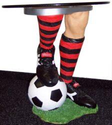 Stolek Fotbal s kulatou deskou-Stolek s kulatou deskou o průměru cca 50cm a opěrnou nohou v designu nohy hráče opřenou o míč. Výška cca 50-60cm.
