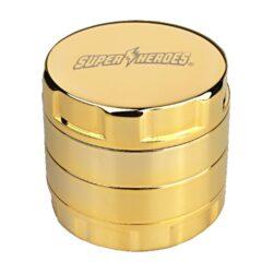 Drtič tabáku SuperHeroes 24K GOLD-Pozlacený kovový drtič tabáku SuperHeroes 24K Gold. Luxusní čtyřdílná drtička se sítkem a zásobníkem na tabák je precizně vyrobena z kvalitní čisté mědi CNC technologií. Hladký vysoce lesklý povrch drtiče je pozlacen 24 karátovým zlatem. Víčko drtičky je zdobené pískovaným logem SH. Jednotlivé díly drtiče se uzavírají na závit mimo horního víčka, které je na magnet. Velmi ostře broušené zuby do špičky ve tvaru diamantu zajistí rychlé nadrcení vaši směs do požadované kvality. Drtič tabáku je dodávaný v dárkové krabičce se sametovým vnitřkem, sáčkem na drtič, leštícím jemným hadříkem a certifikátem o pozlacení 24 karátovým zlatem včetně sériového čísla drtiče. Krásný dárek pro Vaše přátelé, kterým uděláte jistě radost. Rozměry: průměr 53mm, výška 50mm.
